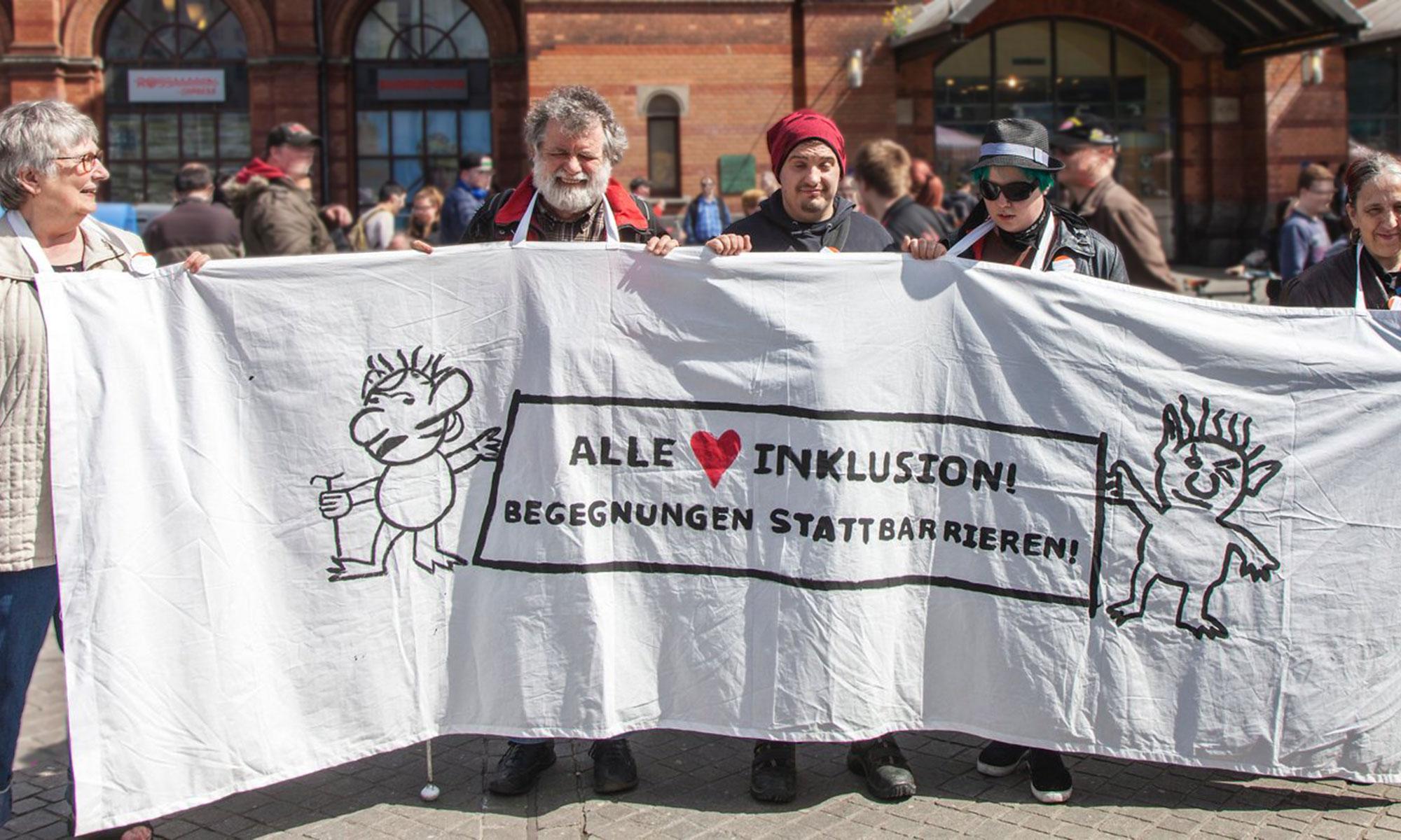 """Blinde Menschen demonstrieren vor dem Hauptbahnhof mit einem Transparent auf dem steht: """"Alle lieben Inklusion! Begegnungen statt Barrieren"""""""